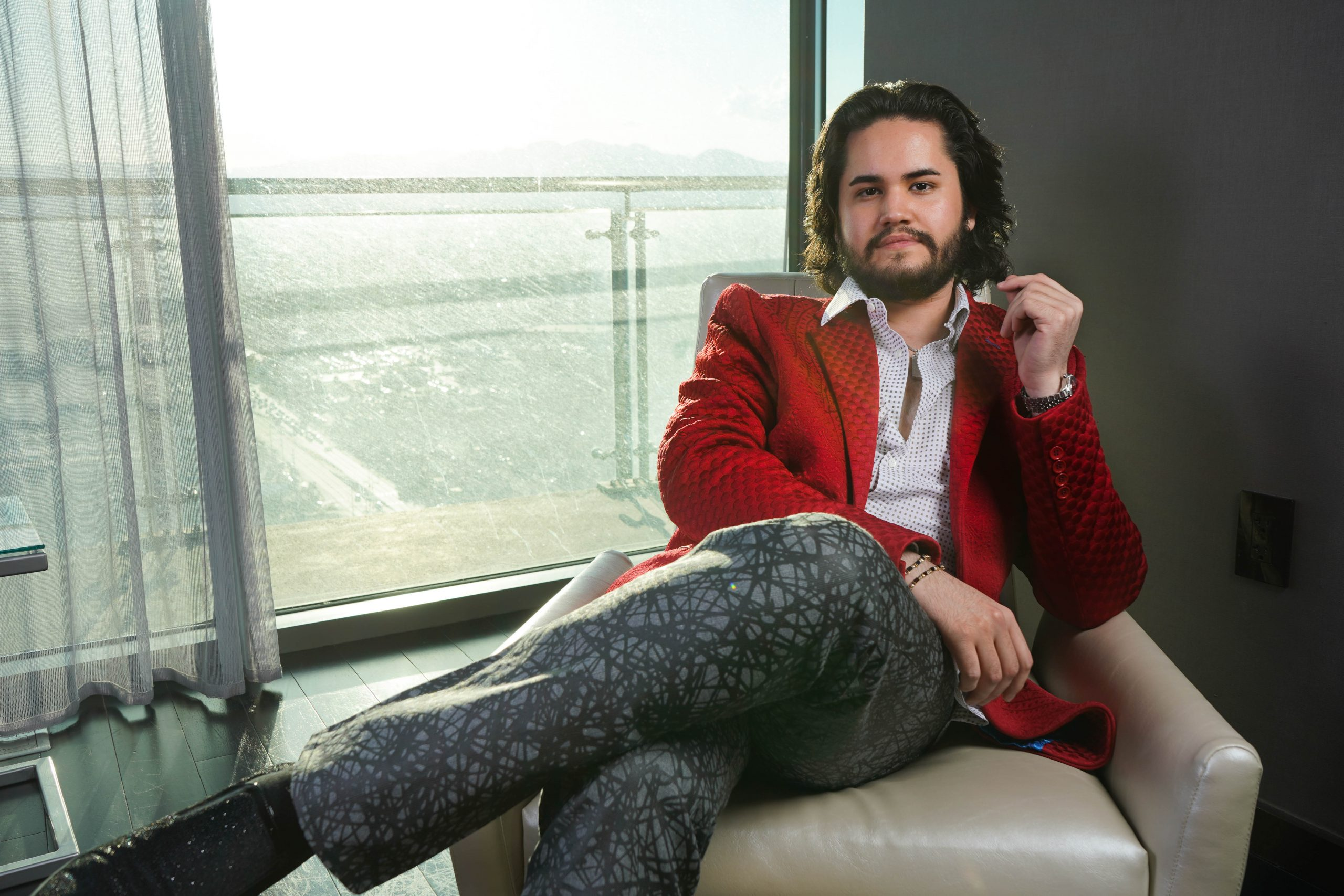 Roman Alexander Wellington in red jacket sitting down in laid back position scaled